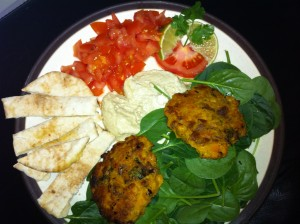 Some sweet potato falafel on a beige place with salad, humous and tomato